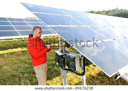 Engineer working with laptop by solar panels, talking on cell phone - stock photo