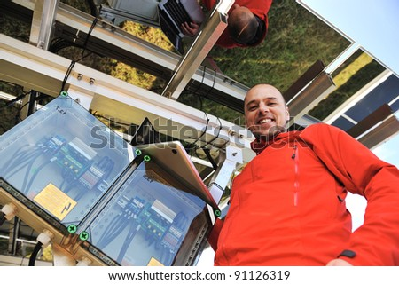 Engineer working with laptop installing  solar panels - stock photo