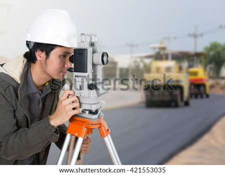 engineer working with survey equipment theodolite with road under construction background