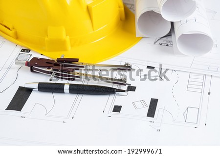 Engineer workplace with blueprints, compass, pen and safety helmet