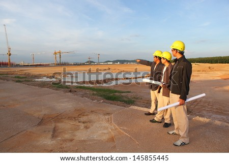 engineer yellow helmet for workers security on the background of a new high-rise apartment buildings and construction cranes and blue sky