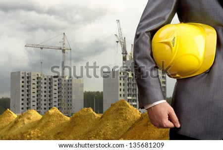 engineer yellow helmet for workers security over new houses and crane background - stock photo