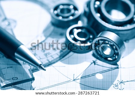 Engineering concept. Few ball bearings near ruler and pen on graph paper background - stock photo