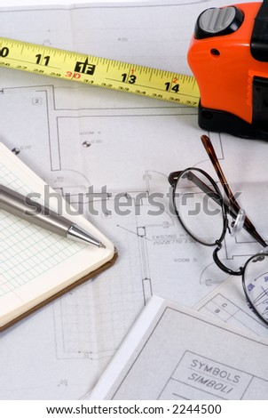 Engineering drawings and tools laid out on a table