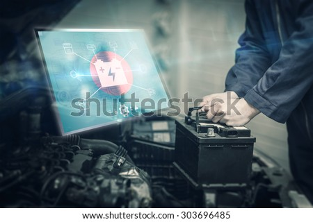 Engineering interface against mechanic changing car battery - stock photo