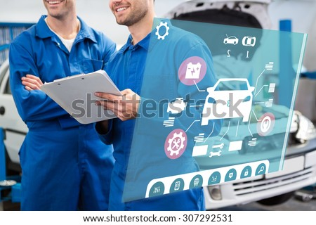 Engineering interface against smiling mechanic working together on clipboard - stock photo
