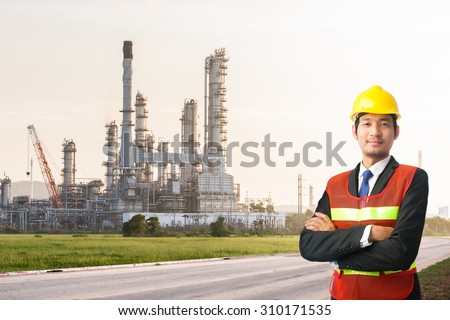 engineering man and safety helmet, shirts standing arms crossed against oil refinery plant in petrochemical industr - stock photo