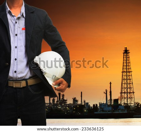 engineering man and safety helmet standing against beautiful dusky sky of oil refinery plant scene use for energy of fossil fuel and industry topic background - stock photo