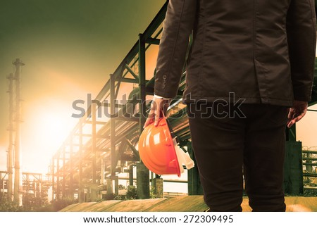 engineering man and safety helmet standing against beautiful light sun shine in heavy petrochemical industry estate  - stock photo