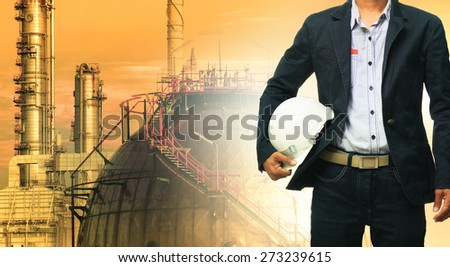 engineering man and safety helmet standing against oil refinery plant in heavy petrochemical industrial estate  - stock photo