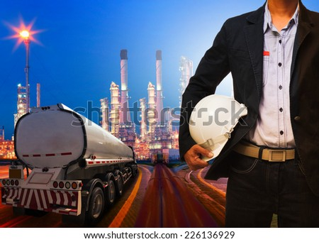 engineering man with safety helmet standing against beautiful lighting of oil refinery plant in heavy petrochemical industry and container truck transportation of petroleum - stock photo