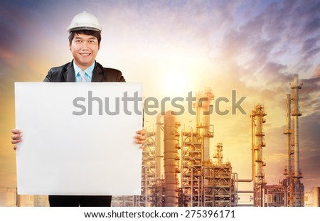 engineering man with white empty white broad standing in front of oil refinery industry estate use for industrial theme - stock photo