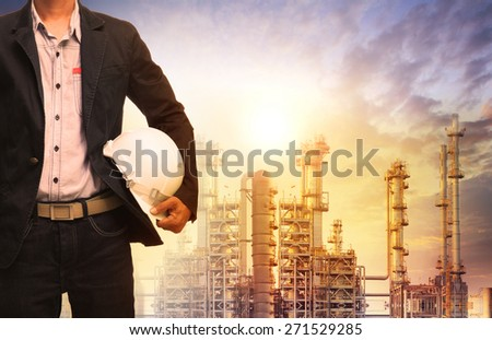 engineering man with white safety helmet standing in front of oil refinery building structure in heavy petrochemical industry  - stock photo
