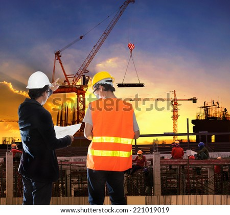 engineering man working in building construction site with worker foreman against beautiful dusky sky - stock photo
