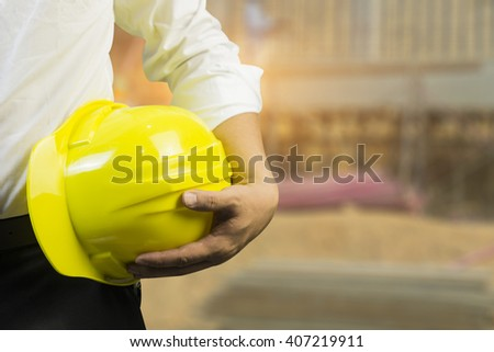 engineering management construction helmet,engineer or worker hold in hand yellow helmet for workers security  on working  site background.  business Man ,management ,selective focus,vintage tone