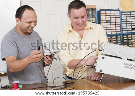 Engineering student and professor using oscilloscope and function generator in electrical engineering laboratory