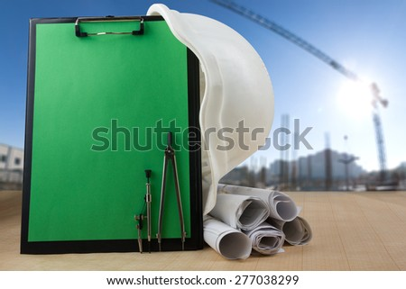 Engineering tools - architectural blueprints, blank clipboard, divider compass, and white safety helmet on graph paper. with sunset scene at building construction site  - stock photo