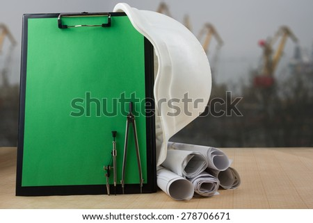 Engineering tools - architectural blueprints, blank clipboard, divider compass, and white safety helmet on graph paper at building construction site - stock photo