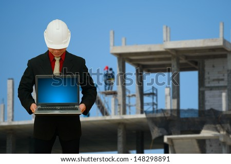 Engineering with laptop in construction yard - stock photo