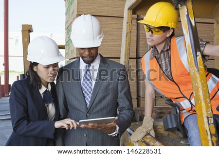 Engineers and female industrial worker looking at tablet PC - stock photo