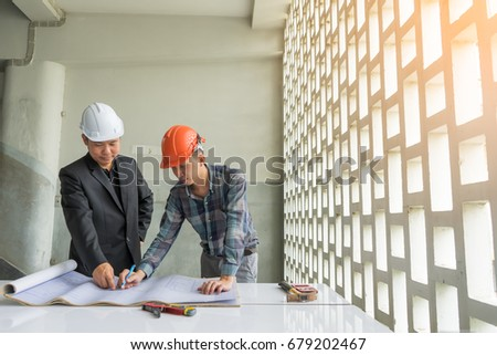 Engineers wearing security helmets while explaning stock photo engineers are wearing security helmets while explaning construction plan looking at blueprint paper construction drawing plan malvernweather Image collections