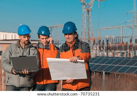 Engineers at Work In a Solar Power Station - stock photo