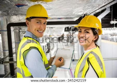 Engineers checking the temperature pipes in the control room - stock photo