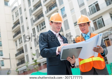 Engineers discussing blueprint of the building at the construction site - stock photo