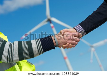 Engineers giving Handshake in a Wind Turbine Power Station Italy - stock photo