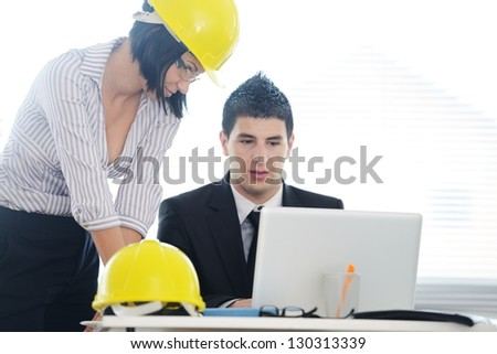 Engineers having discussion about new business project using laptop - stock photo