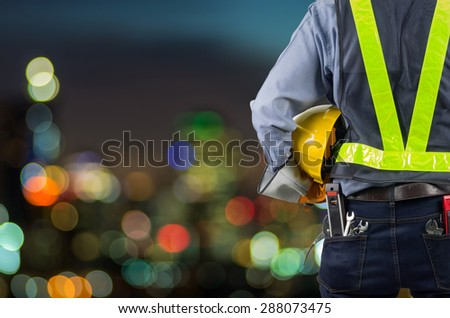 Engineers holding a yellow helmet for the safety of workers. With background blurred light. - stock photo