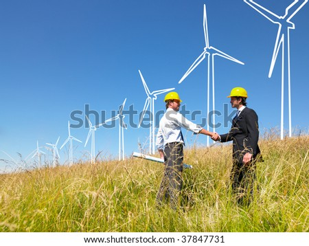 Engineers in field with plans building windmills - stock photo