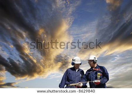 engineers in hard-hats walking under a late dramatic sunset sky, concept image