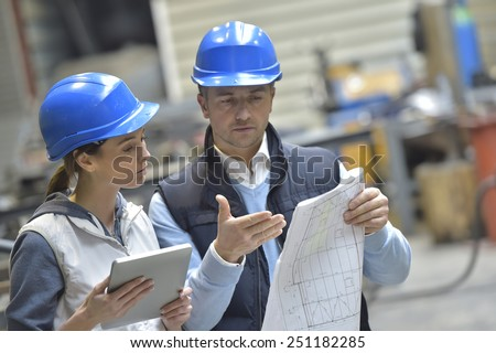 Engineers in mechanical factory reading instructions - stock photo