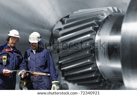engineers, metal-workers, with large steel and titanium gears in background - stock photo