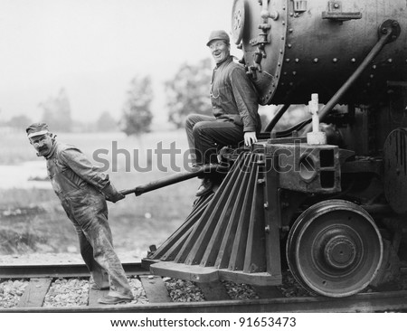 Engineers pulling train engine - stock photo