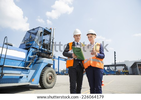 Engineers reading file in shipping yard - stock photo