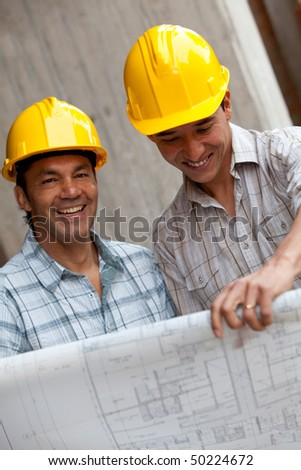 Engineers smiling and holding a model in a construction