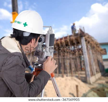 Engineers use tachometer or theodolite with building construction site background - stock photo