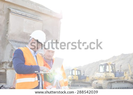 Engineers using laptop at construction site against clear sky - stock photo