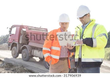Engineers using laptop at construction site against clear sky on sunny day - stock photo