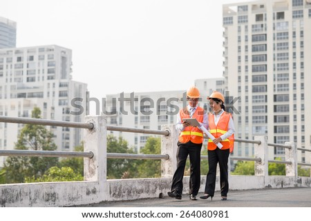 Engineers walking outdoors and discussing construction project on the digital tablet - stock photo