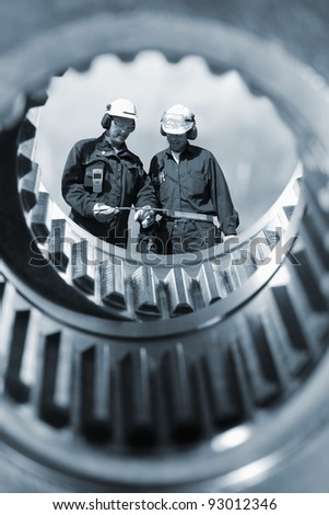 engineers, workers, seen through giant gear wheels, metal blue toning concept - stock photo
