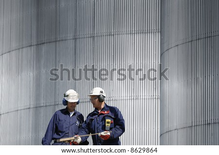 engineers working in front of solid steel background, conceptual image. - stock photo