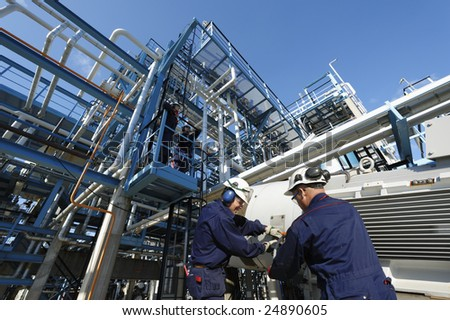 engineers working inside oil and gas refinery, pipelines and storage - stock photo
