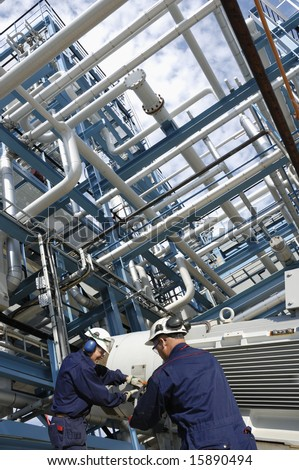 engineers working on giant pipeline pump inside fuel and gas industry, refinery - stock photo