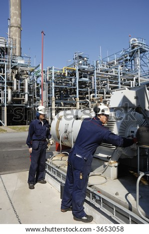 engineers working on main pipeline pump refinery in background, hard-hats and clothing - stock photo