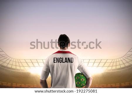 England football player holding ball against large football stadium under blue sky - stock photo