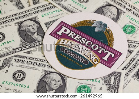 England,London - November 11, 2014:Beermat from Prescott beer and US dollars.Prescott Brewing Company is a full service restaurant,brewery located in the heart of historic downtown Prescott,Arizona - stock photo