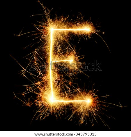 English alphabet from golden sparkler on black background - stock photo